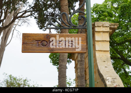 Sign of toilet written on a wooden board. Mark public toilet in the park. - Stock Photo