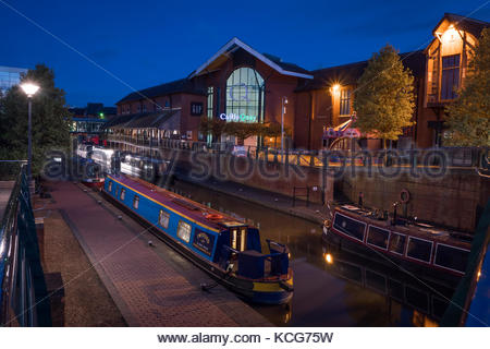 Canal boats moored on the Oxford Canal at Castle Quay Shopping Centre Banbury Oxfordshire England at night - Stock Photo
