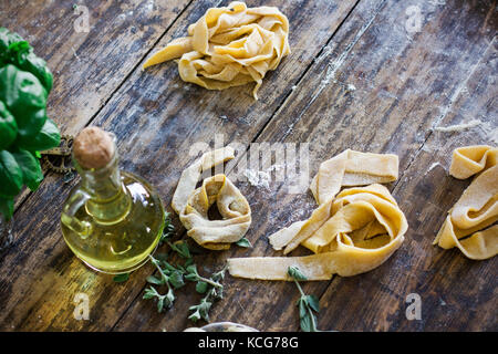Raw homemade pasta on wooden table - Stock Photo
