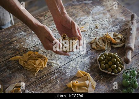 The young man in apron making homemade pasta - Stock Photo