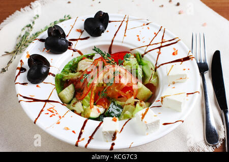 Greek salad in the white deep plate with the fork and knife - Stock Photo