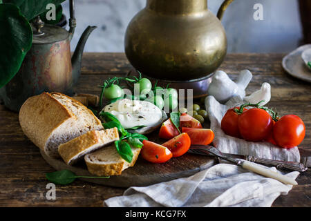 Fresh burrata cheese with tomatoes, Basil and multi-grain bread on the old wooden table. Vegetarian food - Stock Photo
