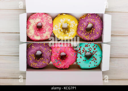 Colorful donuts in the cardboard box on the white wooden background - Stock Photo