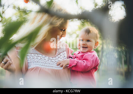 Mother with baby Picking and eating Cherry In Garden - Stock Photo