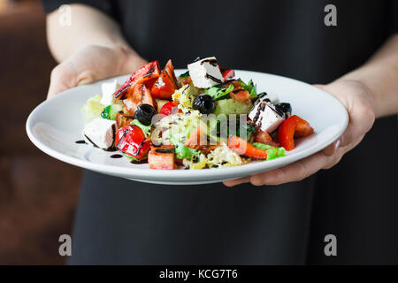 The young female waiter holding in her hands the plate with the Greek salad - Stock Photo