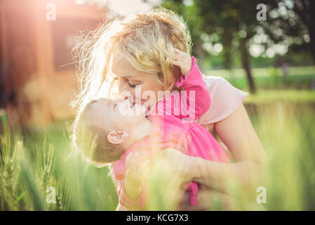 Young mother holding and kissing her baby in the grass - Stock Photo
