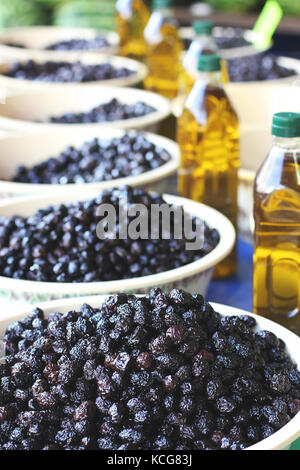 Black pickle olives in bowls and bottles with olive oil at the eastern market - Stock Photo