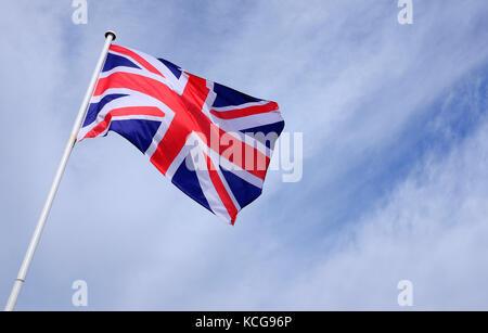 union jack flag flying on blue sky background - Stock Photo