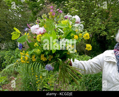 Holding a Peony bouquet in the summer garden - Stock Photo