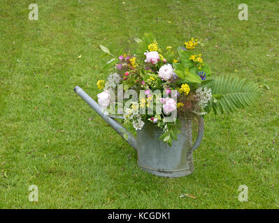 Peony bouquet in a water can in the garden - Stock Photo