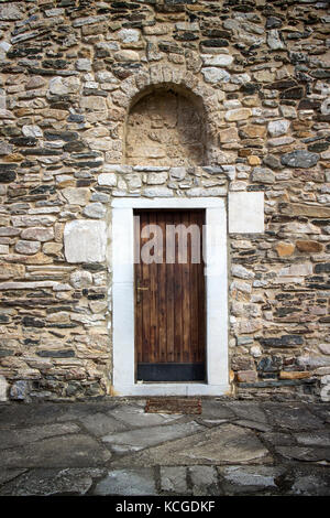 Ancient wooden door in stone castle wall  background - Stock Photo