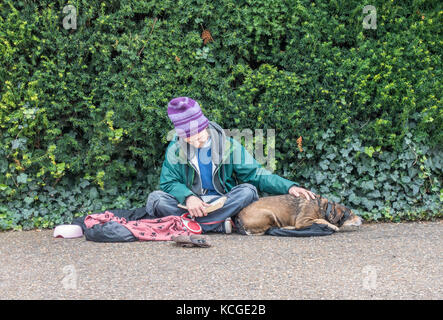 Elderly / old / senior homeless beggar man / rough sleeper, wearing a beanie hat, sitting reading a book with a - Stock Photo