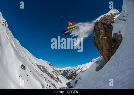 A skier jumps from a rock while skiing off piste in the French ski resort of Courchevel. - Stock Photo