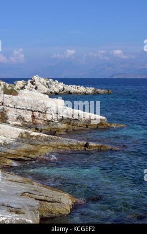 a beautiful Mediterranean rocky coastline in corfu. Crystal claear waters on the rocky beaches at Kassiopi, Corfu, - Stock Photo