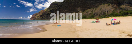 People enjoying the surf at Polihale State Park and its barking sands on the west coast of Kauai, Hawai'i. - Stock Photo