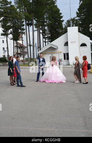 Man and woman prepare for their wedding day with guests watching them - Stock Photo