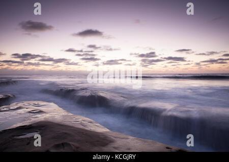 Long exposure shot of rocks and silky water around sunset in La Jolla California coast. - Stock Photo