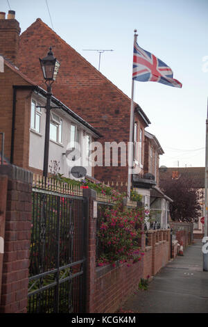 waving UK flag in the blue sky, Union Jack - Stock Photo