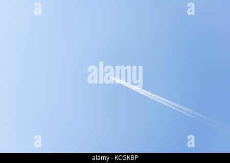 Bright blue summer sky with a single commercial airplane flying. Contrails follow the plane as it speeds through - Stock Photo