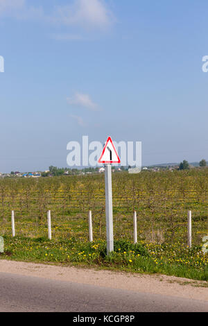 Road sign indicating a steep turn left on the roadway. Photo close up - Stock Photo