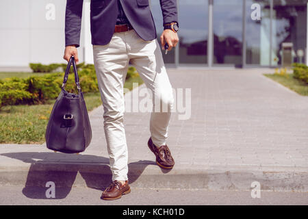 fashionably dressed businessman walks from office building with a bag and car keys in his hand. - Stock Photo