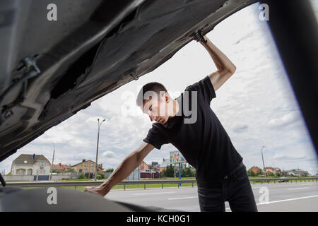 Closeup portrait, young man having trouble with his broken auto, opening hood trying to fix engine, isolated green - Stock Photo
