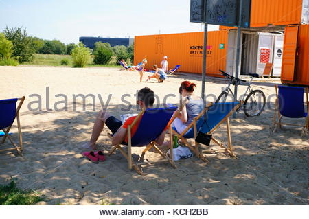 People sitting on sun beds on a sunny day at the city beach on August 2015 in Poznan, Poland - Stock Photo