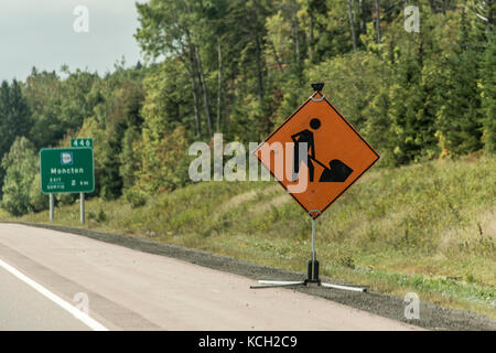 Orange construction worker sign at a road into the distance on trans canada - Stock Photo