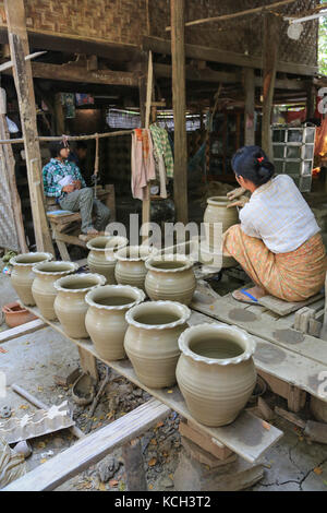 A woman is forming a pot on a pottery wheel in Yandabo Village on the Irrawaddy River in Myanmar (Burma). - Stock Photo