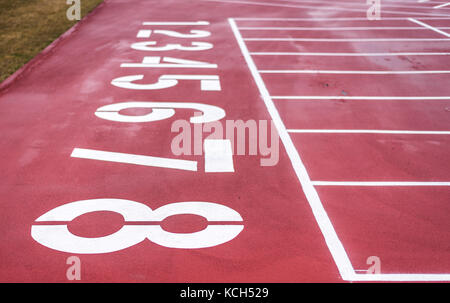 The starting line on a red running track with the lane numbers from eight to one painted in white. - Stock Photo