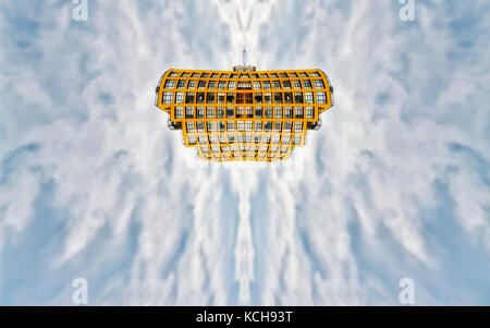 Bright yellow window festooned flying building in a blue sky with light clouds - Stock Photo