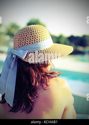 woman wearing a straw hat and she relaxes in the exclusive luxurious tourist resort by the pool - Stock Photo