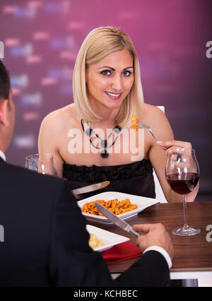 Romantic Couple Sitting Having Dinner In An Elegant Restaurant - Stock Photo