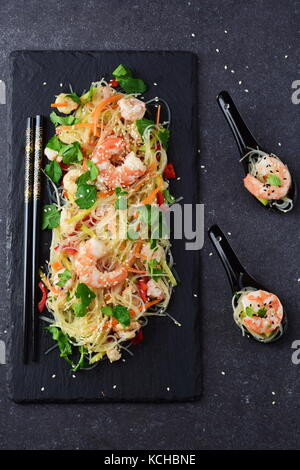 Noodles with prawns and vegetables on a black stone plate and in traditional soup spoons on a grey abstract background. - Stock Photo