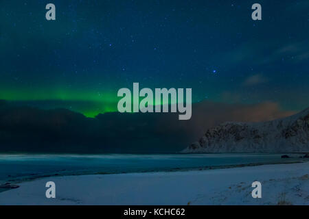 Winter Norway. Night beach among the mountains in Lofoten. Stars in the blue sky and aurora borealis above the clouds - Stock Photo
