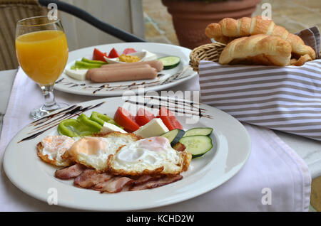 Two plates with nicely served  American breakfast - fried eggs, bacon, sausages - Stock Photo