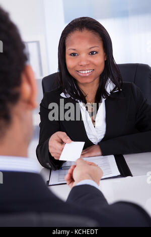 Businesswoman Offering Visiting Card To Man In Office - Stock Photo