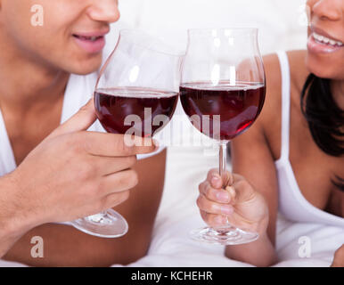 Portrait Of Young Couple Toasting Red Wine On Bed - Stock Photo
