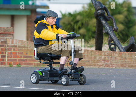 Elderly man riding on an electrically powered mobility scooter, in the UK. - Stock Photo