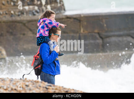 Young girl being carried on woman's shoulders (piggyback ride) on a beach in poor windy weather in Autumn, in Brighton, - Stock Photo