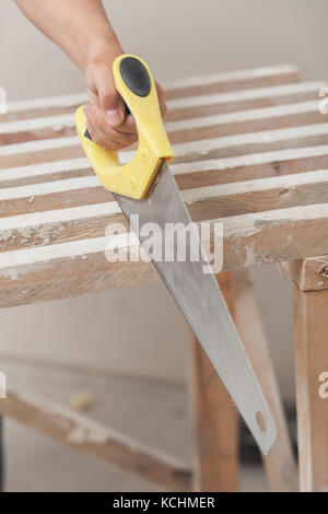 Sawing by the hand saw of wooden whetstone - Stock Photo