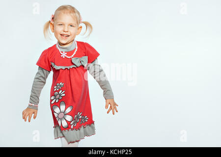 Beautiful baby girl on a white background. Girl goes and grimaces - Stock Photo