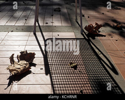 long shadows cast by outdoor chair and dried leaves in low Autumn sun on a terrace in Tuscany, Italy - Stock Photo