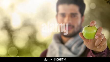Digital composite of Man in Autumn with apple in forest - Stock Photo