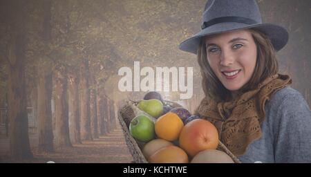 Digital composite of WOman holding fruit basket in Autumn in forest - Stock Photo