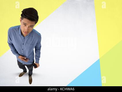 Digital composite of Businessman looking up in strange perspective with triangles - Stock Photo