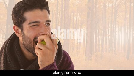 Digital composite of Man in Autumn eating apple in bright forest - Stock Photo