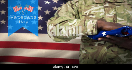 Mid section of soldier holding american flag against logo for veterans day in america - Stock Photo