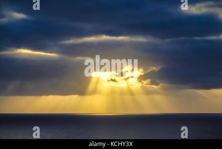 Sunburst through clouds over the ocean - Stock Photo