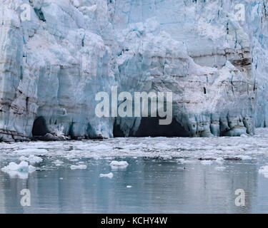 Melting ice leaves caves behind on Margerie glacier in Glacier Bay National Park and Preserve, Alaska - Stock Photo
